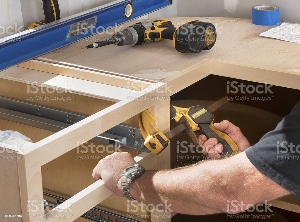Construction Worker Installing Kitchen Cabinets stock photo