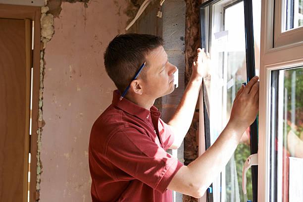 bau arbeiter installieren eine neue fenster im haus - fenster einbauen stock-fotos und bilder