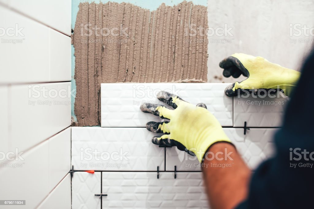 construction worker installing small ceramic tiles on bathroom walls and applying mortar with trowel stock photo