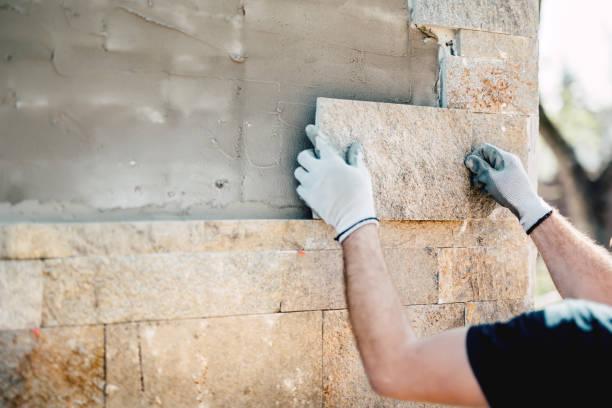 byggnadsarbetare installerar sten på arkitektonisk fasad av nybygge. detaljer för byggbranschen - fasad bildbanksfoton och bilder