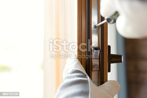 966792200 istock photo Construction worker installing window in house. Handyman fixing the window with screwdriver 966792200
