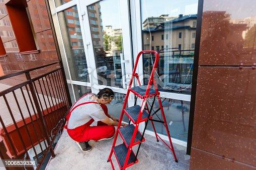 istock Construction worker installing window in house 1006839336