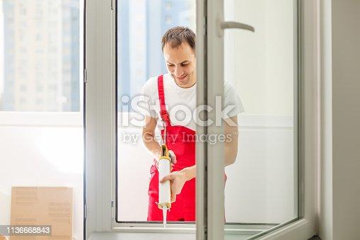 istock Construction worker installing window in house 1136668843