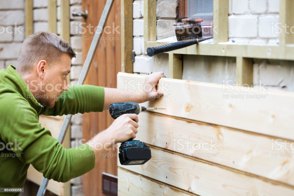 Bauarbeiter, die hölzerne Planken auf Fassade des Hauses zu installieren – Foto