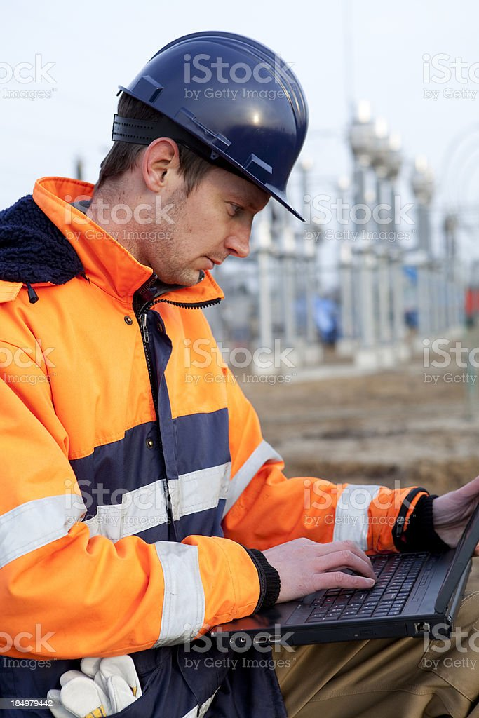 Construction worker is looking on laptop royalty-free stock photo