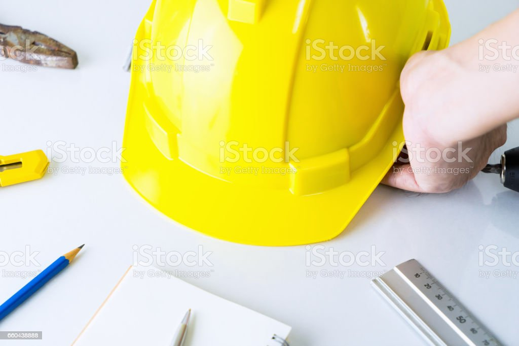 Construction worker is picking up safety helment from tool desk stock photo