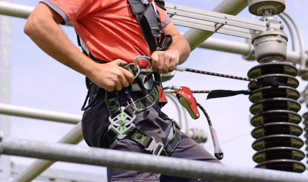 Construction worker is tying the safety harness. Construction harness Electricity pylon, manual worker climbing to repair transmission line. Work at height. safety harness stock pictures, royalty-free photos & images