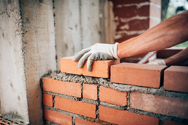 Construction worker laying bricks on exterior walls stock photo