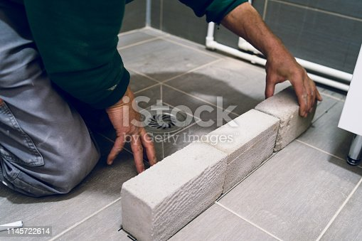 Construction worker laying cement brick wall in the bathroom for the shower ceramic tiles water barrier