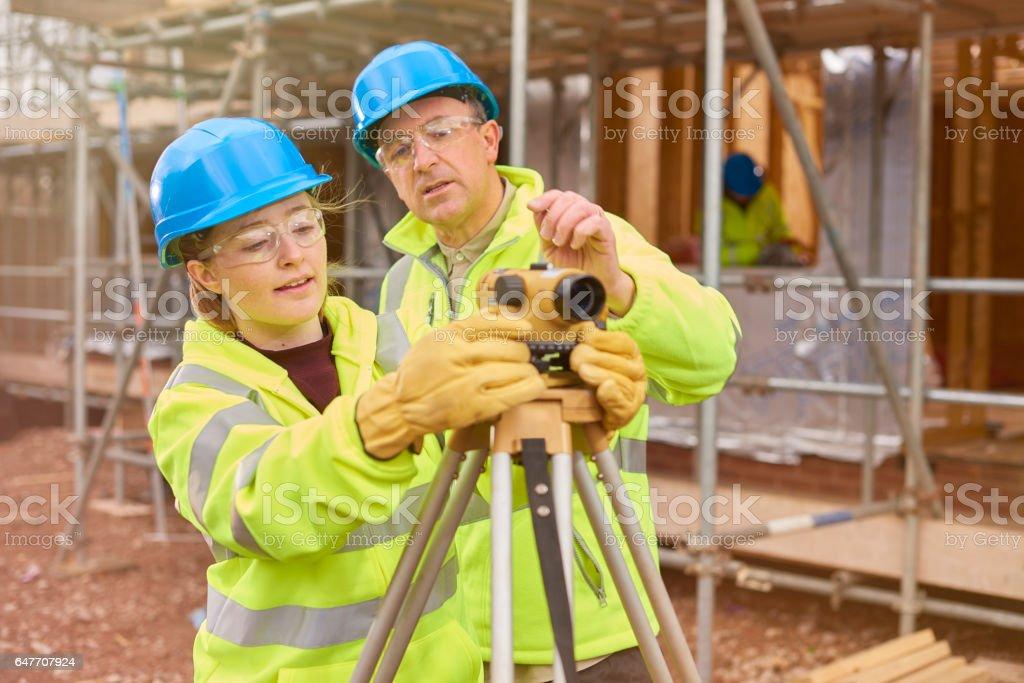 Bauarbeiter, die lernen, wie man ein Baumeister Ebene verwenden – Foto
