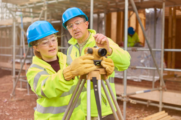 construction worker learning how to use a builder's level a female construction worker stands behind a builder's level on a  building site .Behind her a co-worker walks across the development . apprentice stock pictures, royalty-free photos & images