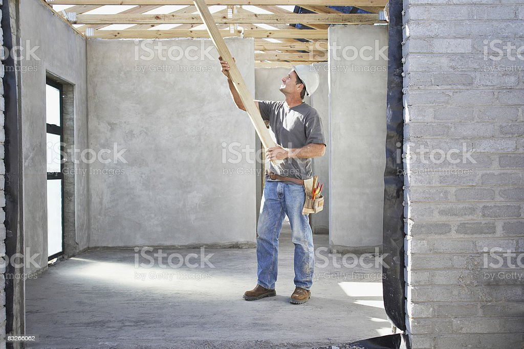Construction worker lifting lumber on construction site royalty free stockfoto