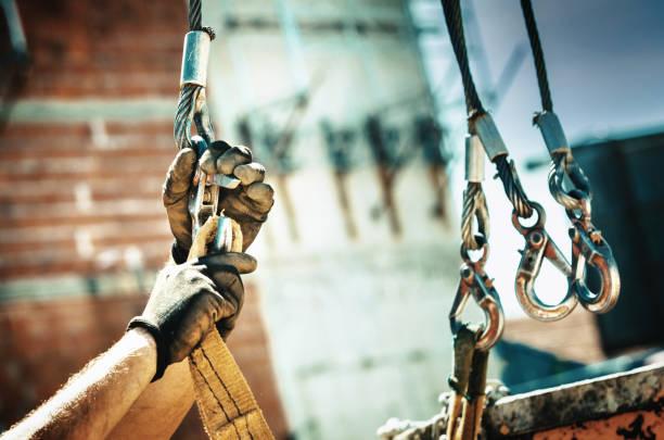 Construction worker loading cargo onto a construction crane stock photo