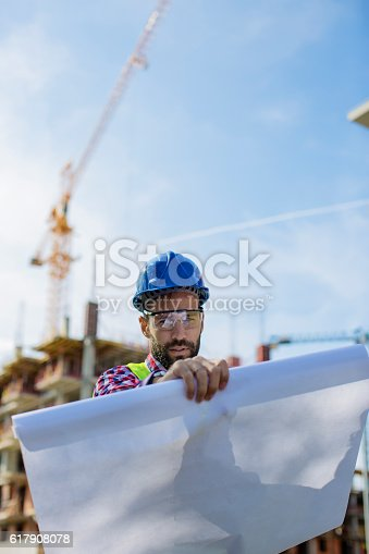 617878058 istock photo Construction worker looking at blueprints 617908078