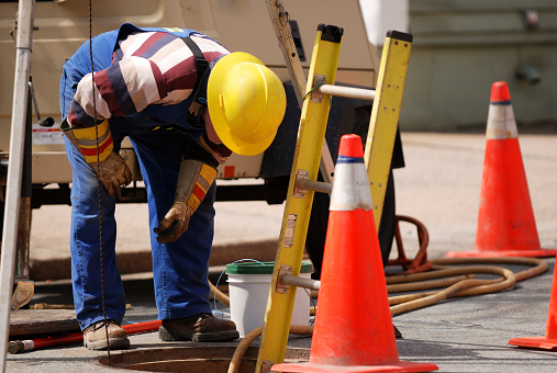 A construction worker looks down a man hole.  He is bent over wearing safety gear, hard hat and gloves.  There is a ladder down and safety cones for traffic control.