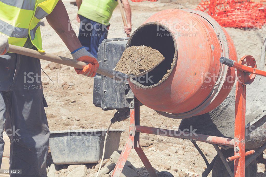 Construction worker making concrete in the mixer. stock photo