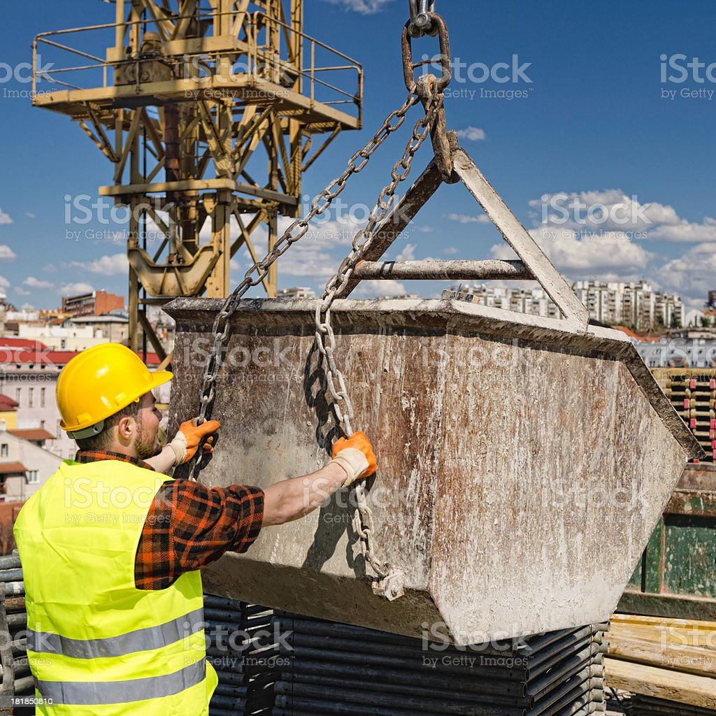 Construction worker manouvering with concrete crane basket stock photo