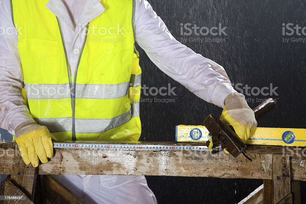 Construction worker measuring using ruler and level. Deadlines are short. royalty-free stock photo