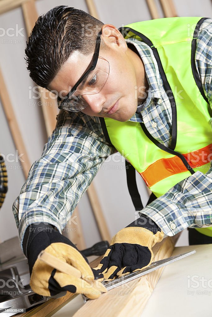 Construction worker measuring wood royalty-free stock photo