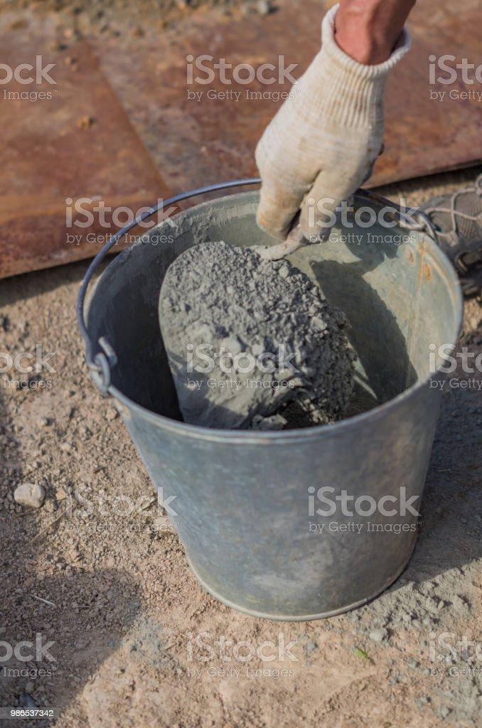 trabajador de la construcción mezcla cemento concreto y arena por espada. - foto de stock
