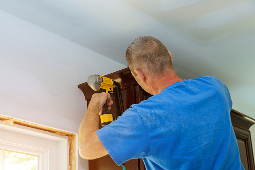 istock Construction worker nailing brad nail air gun to crown moulding on white kitchen cabinets 1185222381