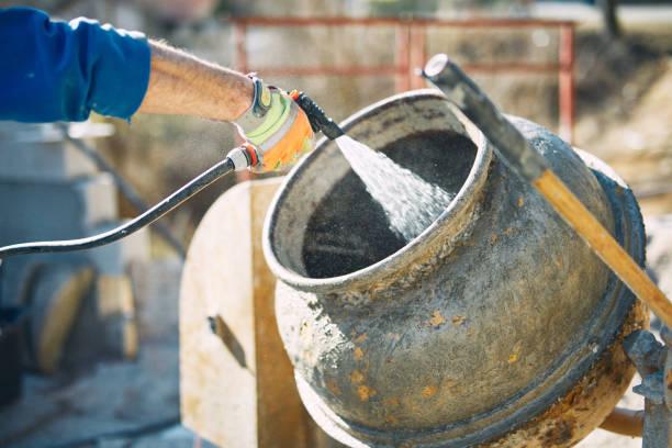 Bauarbeiter auf einem Zement/Betonmischer reinigen restlichen Zement. – Foto