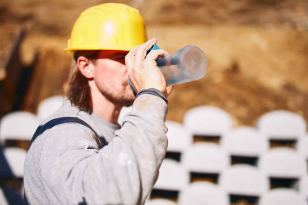 Construction worker on a heavy site doing hard work and drinking water. stock photo