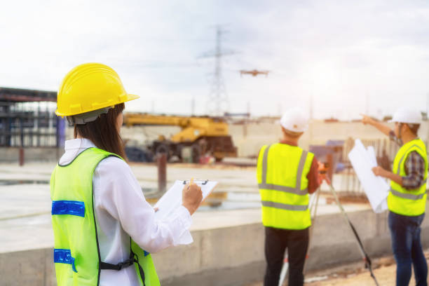 Construction worker on building with drone. stock photo