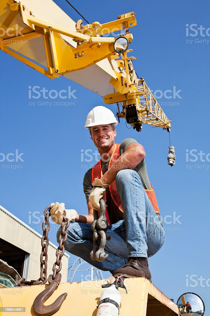 Construction worker on crane with steel hook stock photo