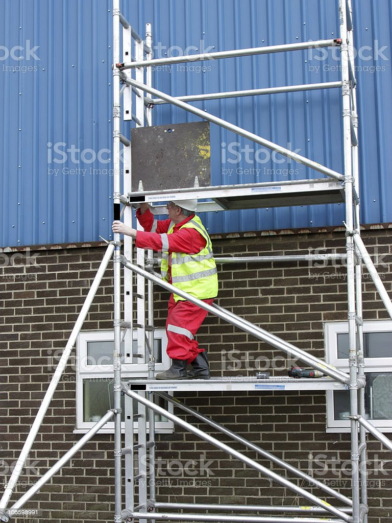 construction worker on portable scaffolding stock photo