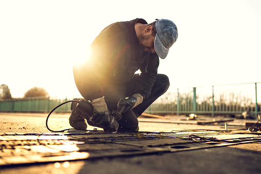 Manual worker using grinder and working on road reparation on bridge at sunset.