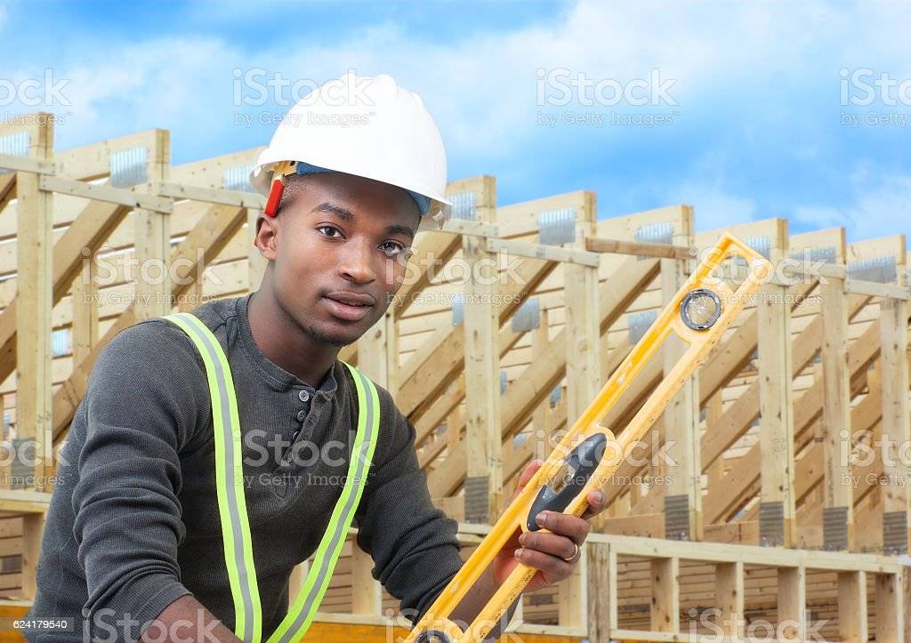 construction worker on site holding level with white helmet stock photo