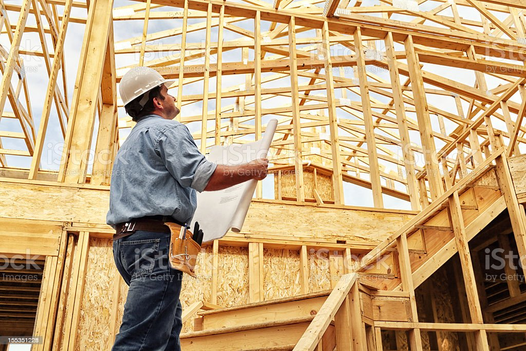 Construction Worker on Site with Plans stock photo