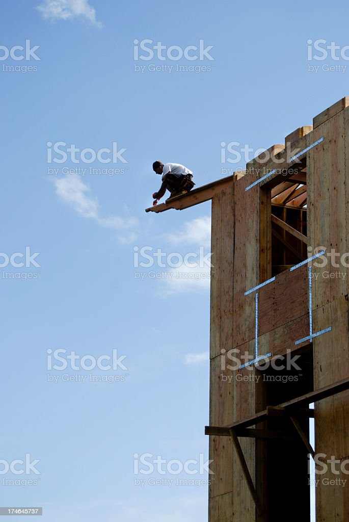 Construction worker on the edge of the top of a building stock photo