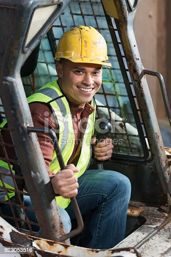An Hispanic construction worker at a job site, sitting in a backhoe, wearing a yellow hardhat and safety vest. He is getting ready to climb out, smiling and looking at the camera.