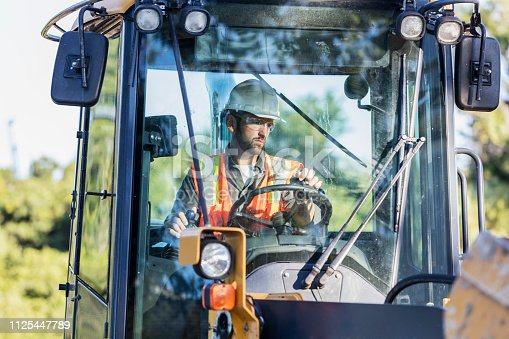 A mid adult man in his 30s working at a construction site, operating a backhoe. He is wearing a hardhat, safety vest and protective eyewear.