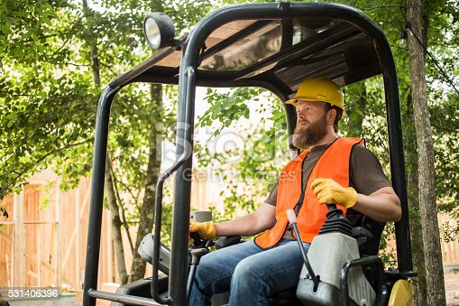 One mid-adult construction worker busy working outside a job site.   The bearded man is working outside of a framed house or small commercial building.  He is operating a small bulldozer and wearing an orange safety vest and a yellow hard hat.