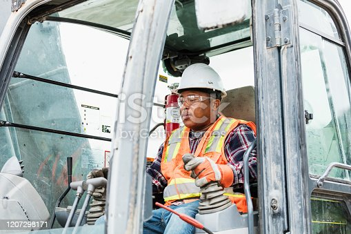 A mature African-American man working at a construction site, driving an earth mover. He is wearing a hardhat, reflective vest, safety goggles and work gloves.