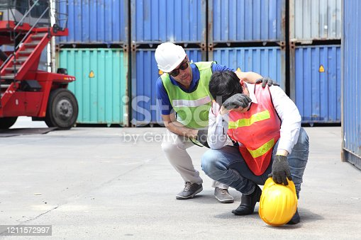 Construction worker or Industrial Engineers has an accident while working on Container ship in import and export business logistic company. Industry and Transportation concept.