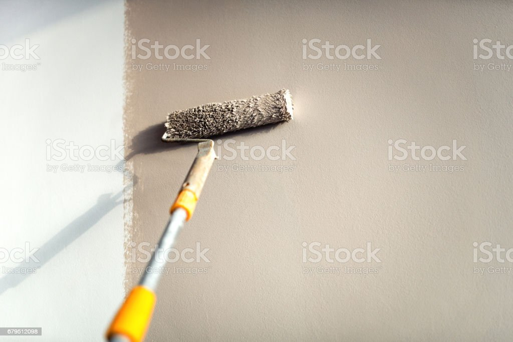 construction worker painting walls using paint roller. royalty-free stock photo