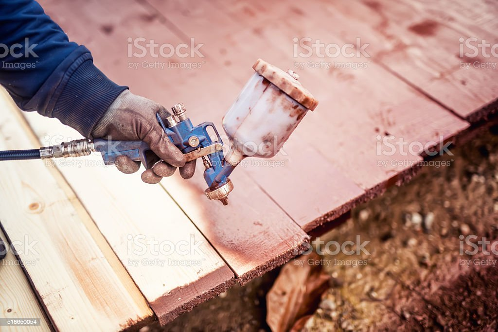 construction worker painting with spray gun stock photo