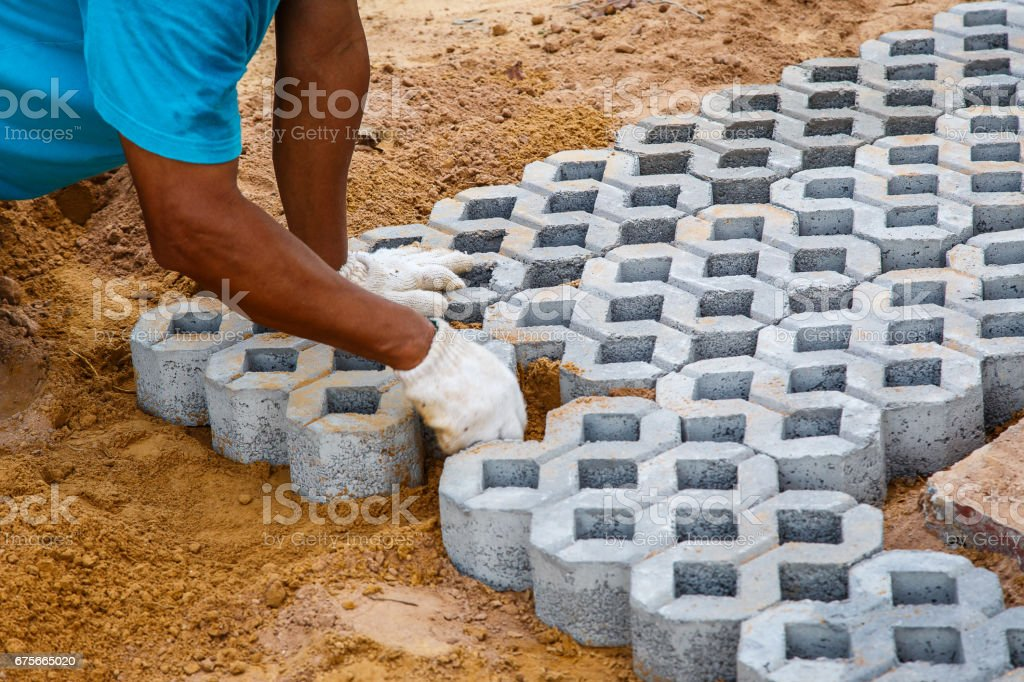 Construction worker paving new parking places, paving block turf stone royalty-free stock photo