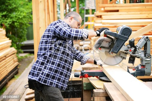 construction worker on a background of a frame house
