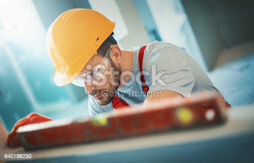 Closeup of mid 30's handsome construction worker checking if the wall is absolutely horizontal. He has short beard and mustache, wearing red uniform, gloves and helmet.Tilt shot, toned.