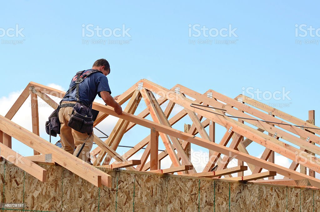 Construction worker piecing together a house frame stock photo