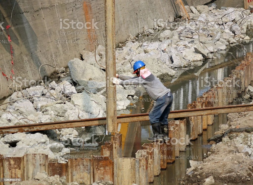 A construction worker places a steel girder stock photo