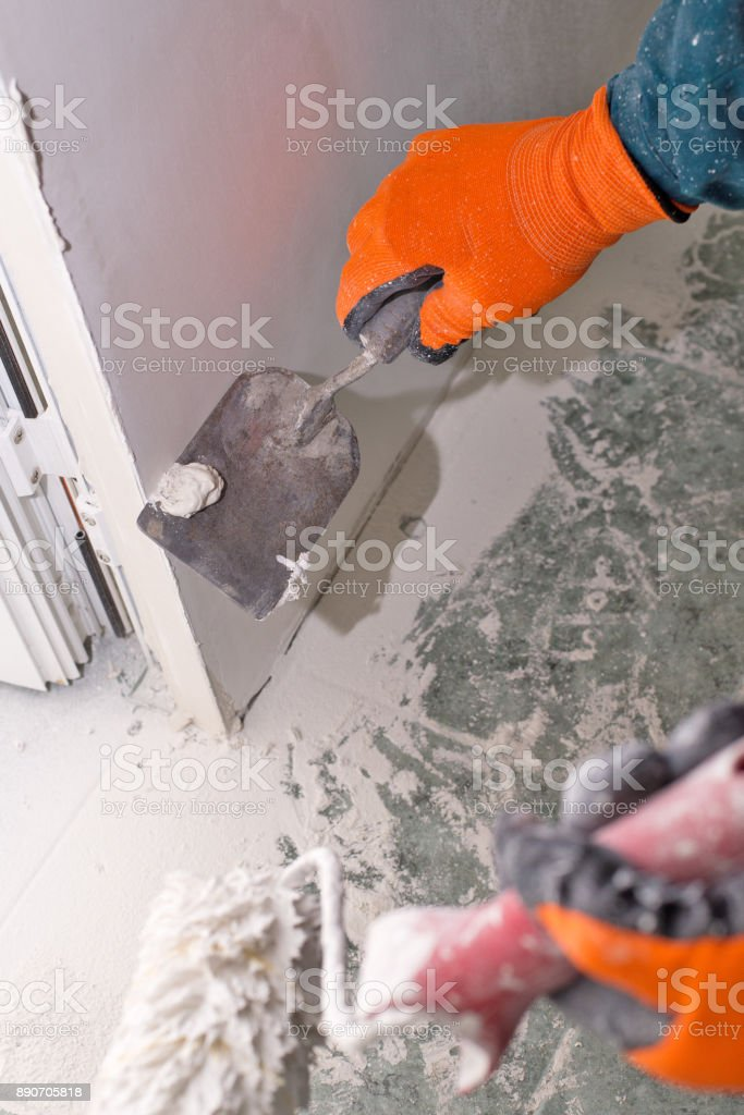 Construction worker plastered wall with a spatula. stock photo
