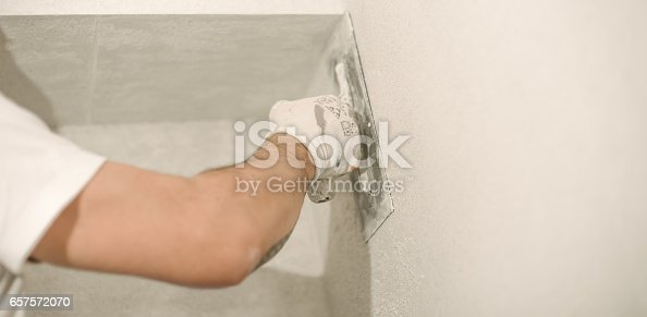 istock Construction worker plastering a wall with a spatula 657572070