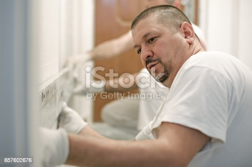 istock Construction worker plastering a wall with a spatula 657602676