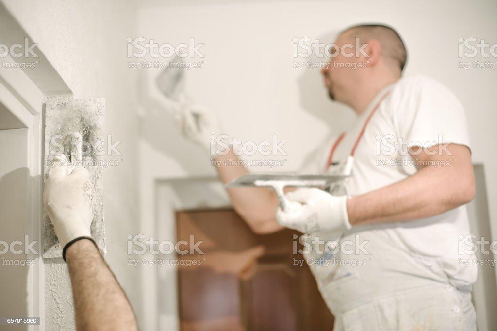 Construction worker plastering a wall with a spatula stock photo